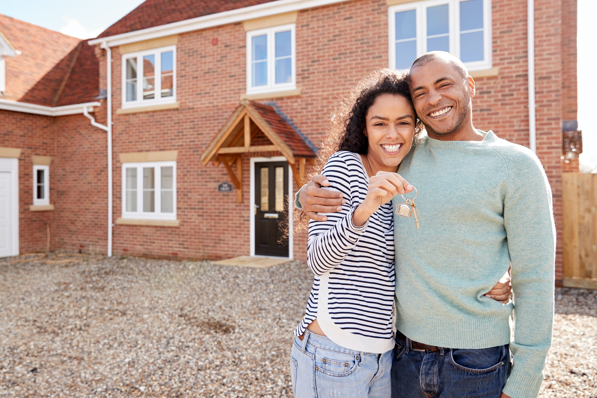 First time home buyer Holding Keys Standing Outside New Home On Moving Day